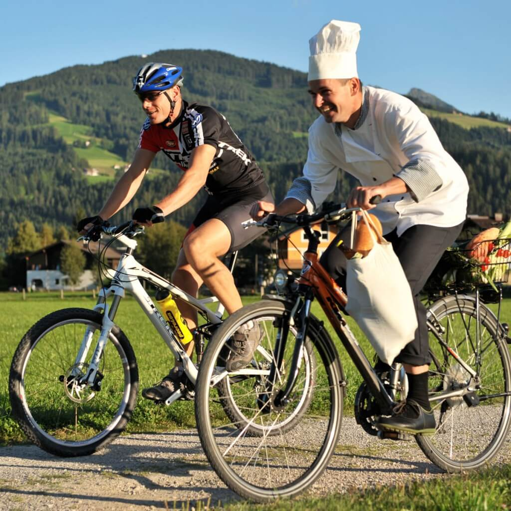 Koch bringt frische Lebensmittel mit dem Rad in das Hotel Zauchenseehof