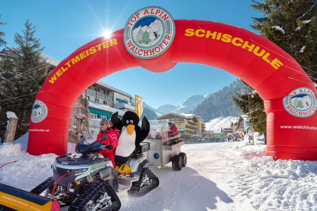 Kinder mit dem Maskottchen Bobo auf dem Weg in die Kinder-Skischule