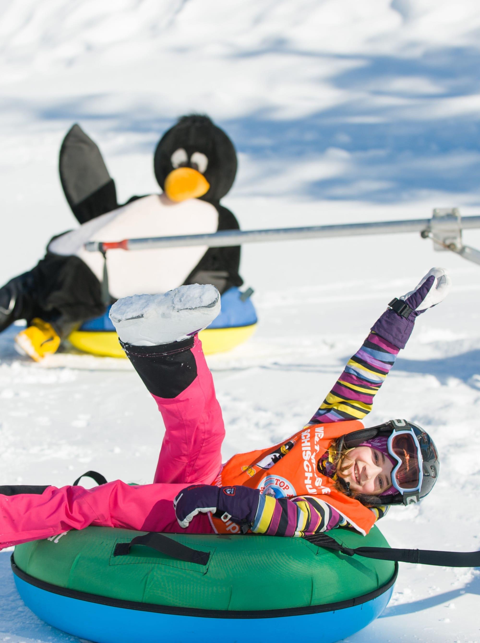 Kind auf aufblasbarem Reifen im Schnee in Zauchensee