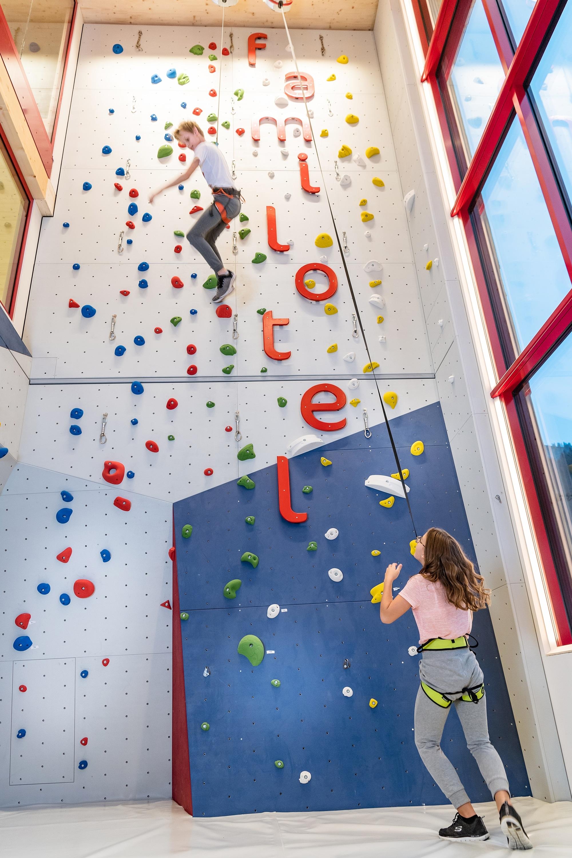 Kinder klettern gesichert auf die Kletterwand im Familienhotel Zauchenseehof