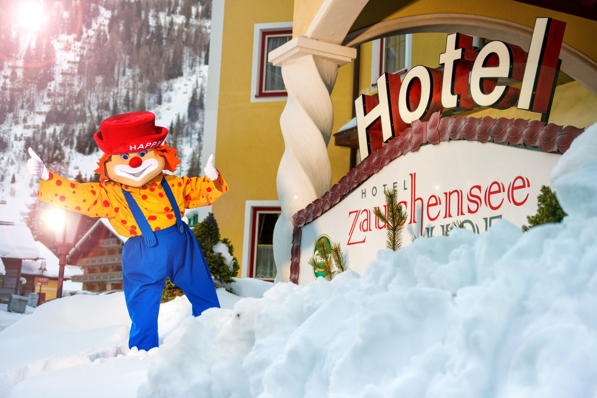 """Maskottchen """"Happy"""" vor dem verschneiten Hotel Zauchenseehof"""