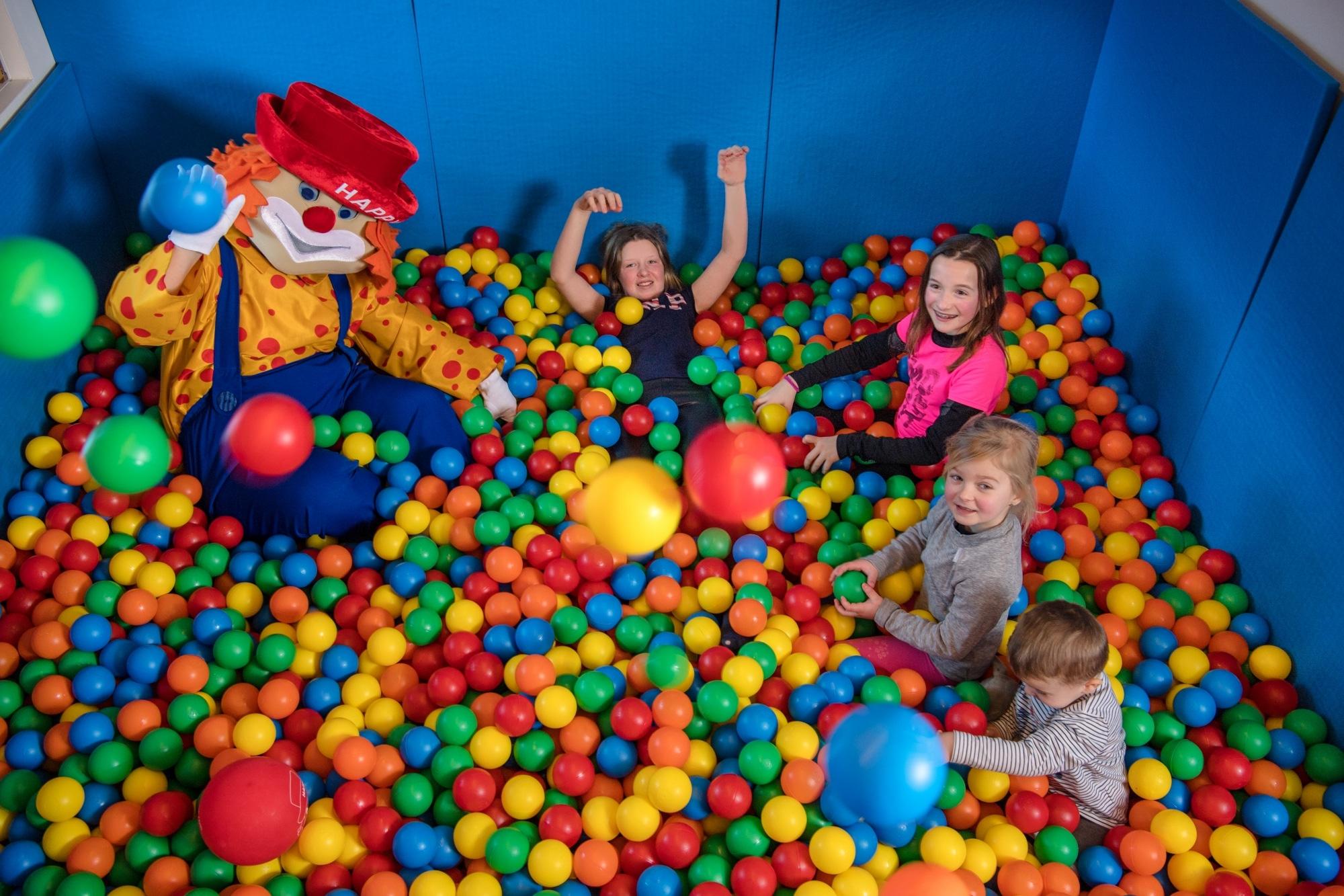 """Kinder im Bällebad mit Maskottchen """"Happy"""" im Familienhotel Zauchenseehof"""