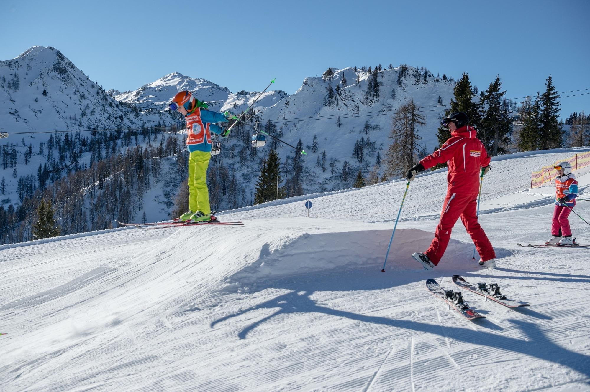 Kind springt mit Skiern über eine Schanze in Zauchensee