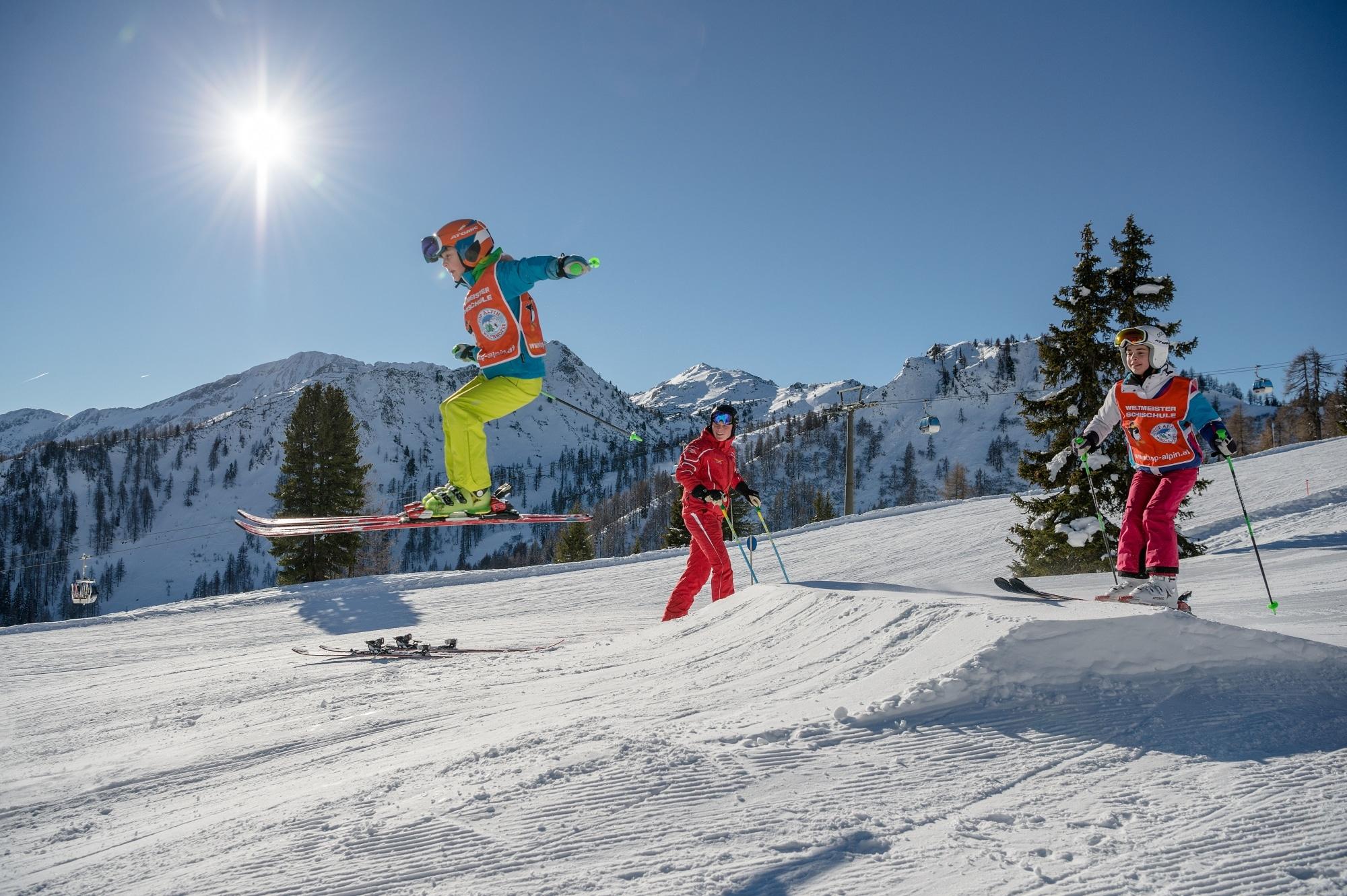 Kinder beim Skifahren und Springen in Zauchensee