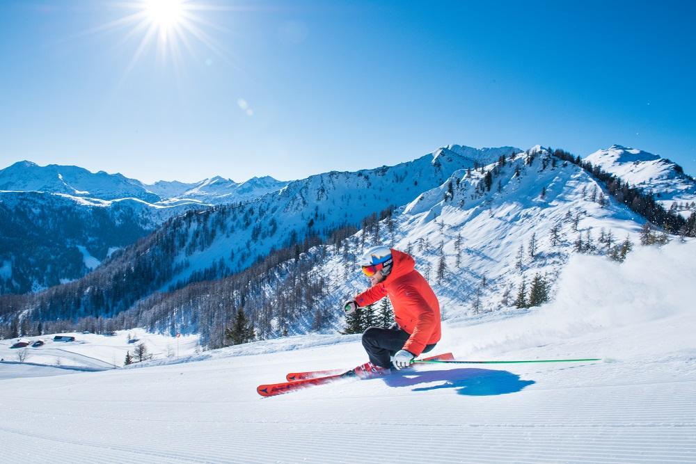 Mann fährt Ski im sonnigen Zauchensee