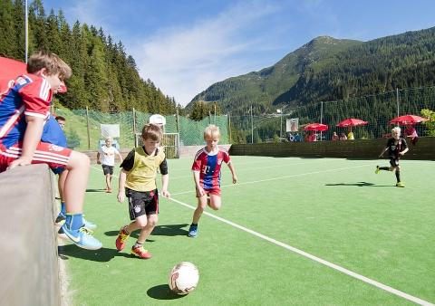 Kinder beim Fußballspielen im Freien in Zauchensee