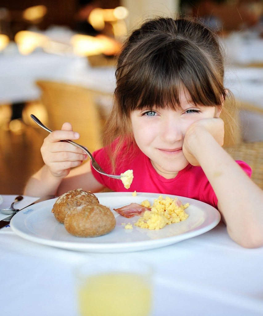 Kleines Mädchen isst ihr Frühstück im Familienhotel Zauchenseehof
