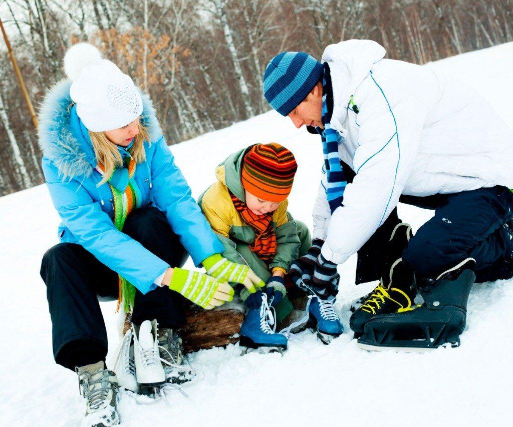 Eltern helfen dem Kind beim Anziehen der Schlittschuhe