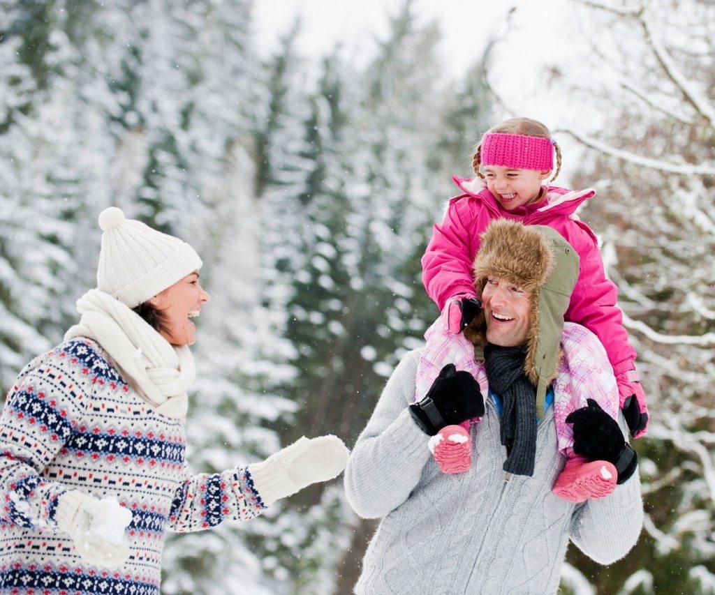 Mädchen sitz auf den Schultern ihres Papas bei einer Schneewanderung